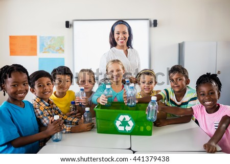 Portrait of pupils and teacher recycling in classroom - stock photo