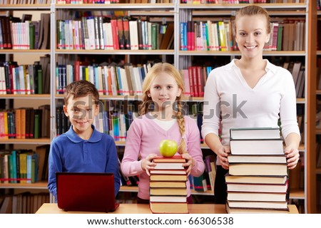 Portrait of pupils and teacher with heaps of books in library - stock photo