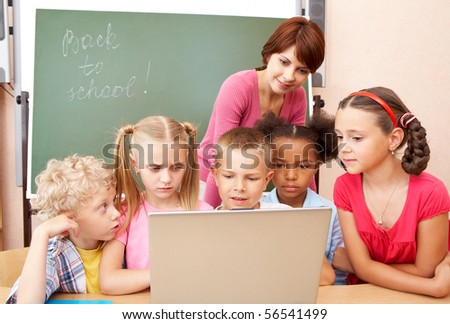 Portrait of pupils looking the laptop with teacher near by - stock photo