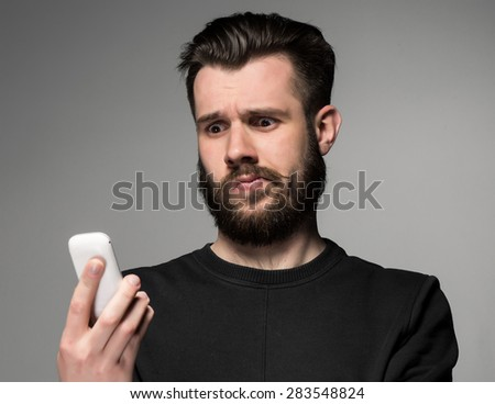 Portrait of puzzled man talking on the phone on a gray background - stock photo