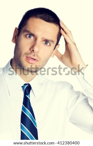 Portrait of puzzled young businessman - stock photo