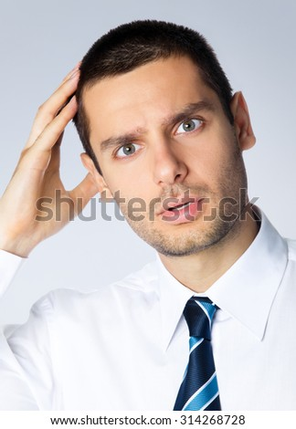 Portrait of puzzled young businessman, posing at studio, against grey background - stock photo