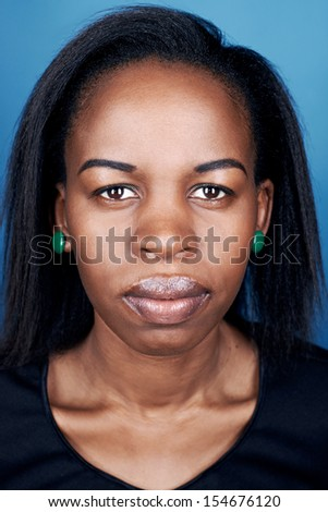 Portrait of real black african woman on blue background - stock photo