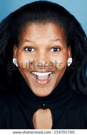 portrait of real funny face african woman on blue background