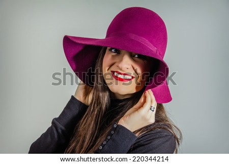 Portrait of real young girl with garnet hat on her head over a gray background - stock photo