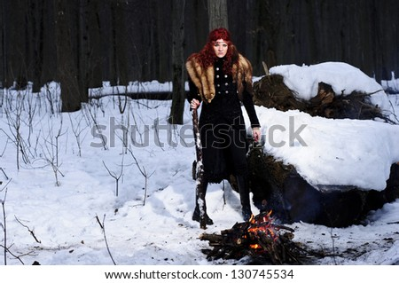 Portrait of red haired beautiful and wild yang woman the hunter in the winter gloomy forest.