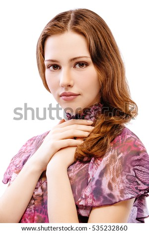 portrait of red-haired girl in colorful blouse posing with arms on her chest