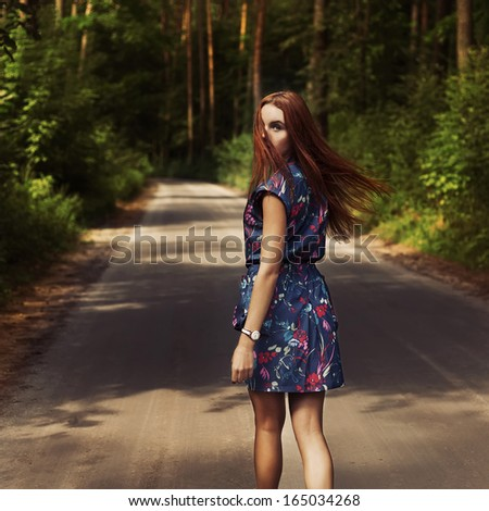 Portrait of red-haired girl in the woods - stock photo