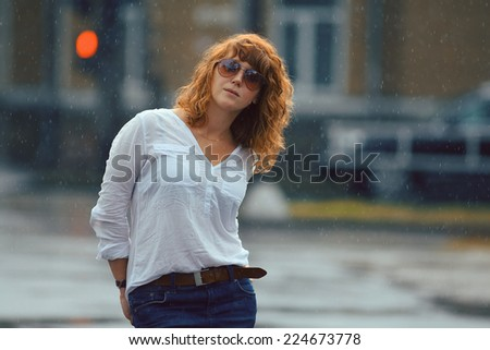 Portrait of red-haired happy woman in the rain - stock photo