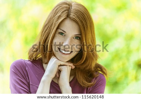 Portrait of red-haired smiling beautiful young woman, against green of summer park.
