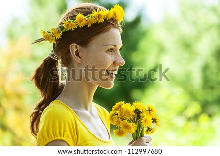 Portrait of red-haired smiling beautiful young woman in yellow blouse with wreath and bouquet of dandelions, against green of summer park.