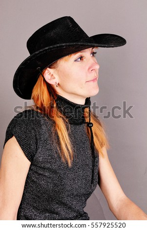 Portrait of red-haired woman in a hat.