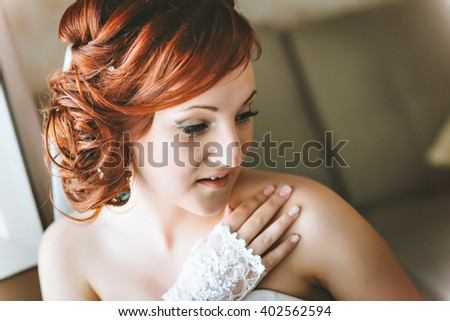 portrait of red-haired young bride, smiling, hand on shoulder.