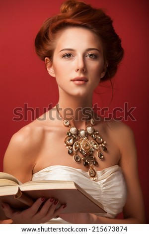 Portrait of redhead edwardian women with book on red background. - stock photo