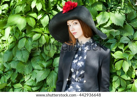 Portrait of redhead girl in vintage hat with flower at green leaves background