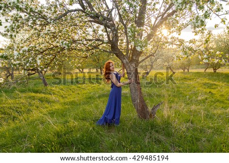 Portrait of redhead girl near blooming apple tree in sunset time