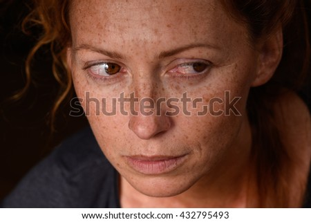 Portrait of redhead woman anxiety expression with tears in eyes trying not to cry suppressed emotion looking back