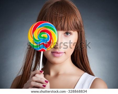 portrait of redhead woman with big lollipop - stock photo