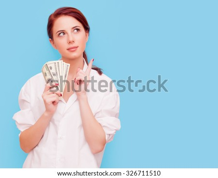 Portrait of redhead woman with money on blue background - stock photo