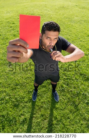 Portrait of referee showing red card as a symbol of dismissal - stock photo