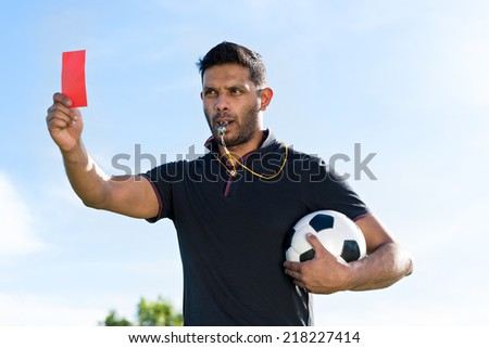 Portrait of referee with a ball showing red card and whistling - stock photo