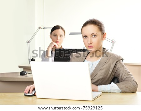 Portrait of relaxed and happy business woman in an office environment working with laptop - stock photo