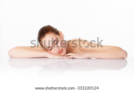 portrait of relaxed beautiful young girl lying her face down on white glass for fresh natural skincare,studio shot,white background - stock photo