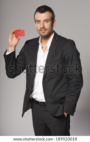 Portrait of relaxed fashionable man in suit showing red card in hand, against gray background - stock photo