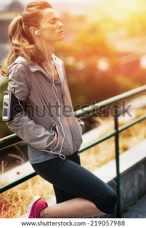 Portrait of relaxed fitness young woman in city in the evening - stock photo