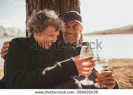 Portrait of relaxed mature couple having a glass of wine at campsite. Senior man and woman toasting wine at on summer day. - stock photo