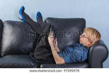 Portrait of relaxed middle aged woman using tablet PC on couch