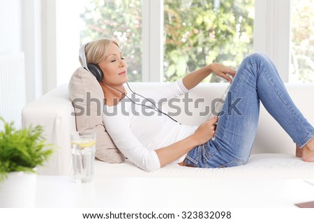 Portrait of relaxed woman with headphone sitting at sofa and listening music on digital tablet. - stock photo