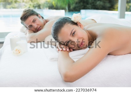 Portrait of relaxed young couple lying on massage table at spa center - stock photo