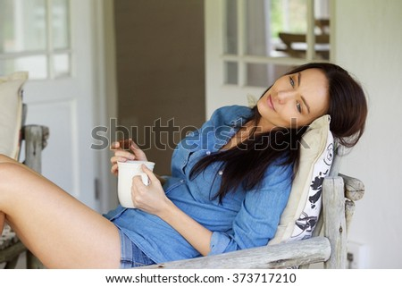 Portrait of relaxed young woman daydreaming with cup of tea at home - stock photo