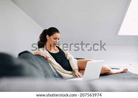 Portrait of relaxed young woman sitting on couch using her laptop. Caucasian female model working on laptop at home. - stock photo