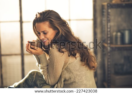 Portrait of relaxed young woman with cup of coffee in loft apartment - stock photo