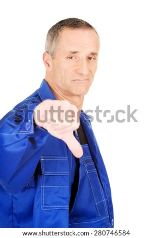 Portrait of repairman showing thumbs down. - stock photo