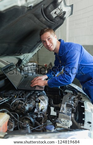 Portrait of repairman using laptop on car engine - stock photo