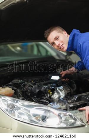 Portrait of repairman with flash light examining car engine - stock photo