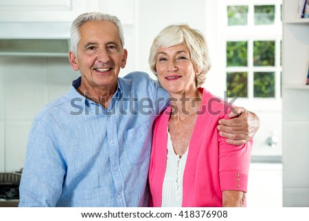 Portrait of retired couple with arm around while standing at home - stock photo