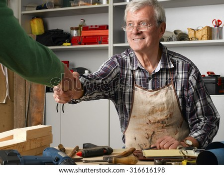 Portrait of retired manual worker sitting at desk in his workshop and shaking hands with casual man.  - stock photo