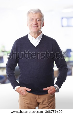 Portrait of retired professional man standing at office. Old casual businessman looking at camera and smiling.  - stock photo