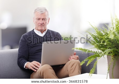 Portrait of retired professional man using laptop while working at home.  - stock photo