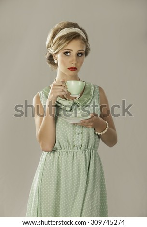 Portrait of retro fifties lady with teacup and saucer - stock photo