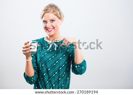 Portrait of retro woman pointing on glass of milk.Milk for you