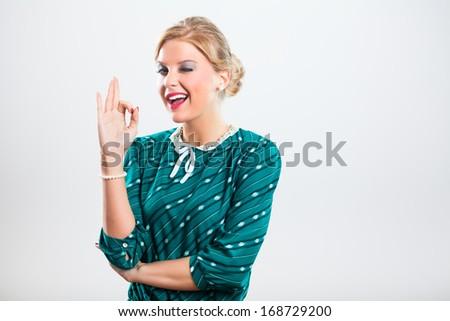 Portrait of retro woman winking and showing ok sign,Retro women winking - stock photo