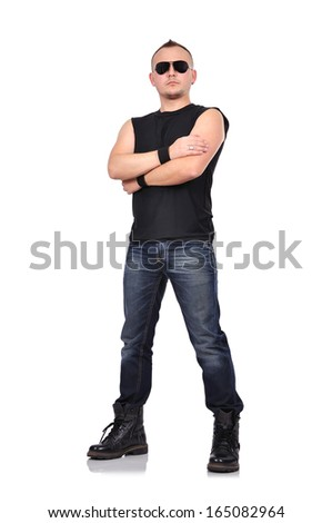 portrait of rocker boy standing with arms folded - stock photo