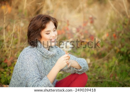 Portrait of romantic beautiful woman with dandelions. Outdoors. - stock photo