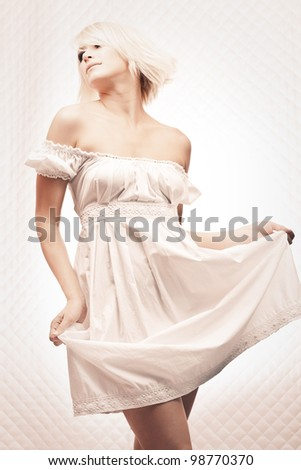 Portrait of romantic blond woman in long white dress