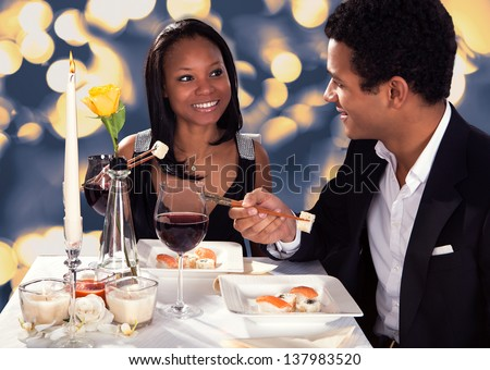 Portrait Of Romantic Couple Eating Sushi At Dinner - stock photo